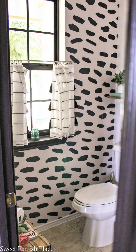 powder room refresh with wallpaper accent wall and black window frame