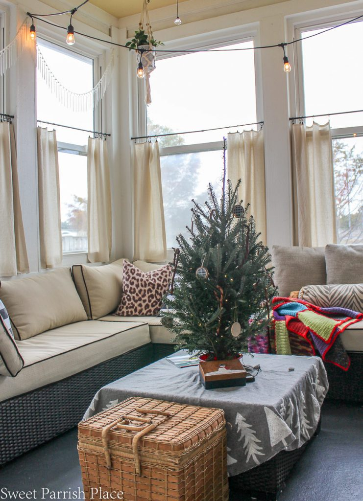 cozy and casual Christmas  sunroom with small real tree
