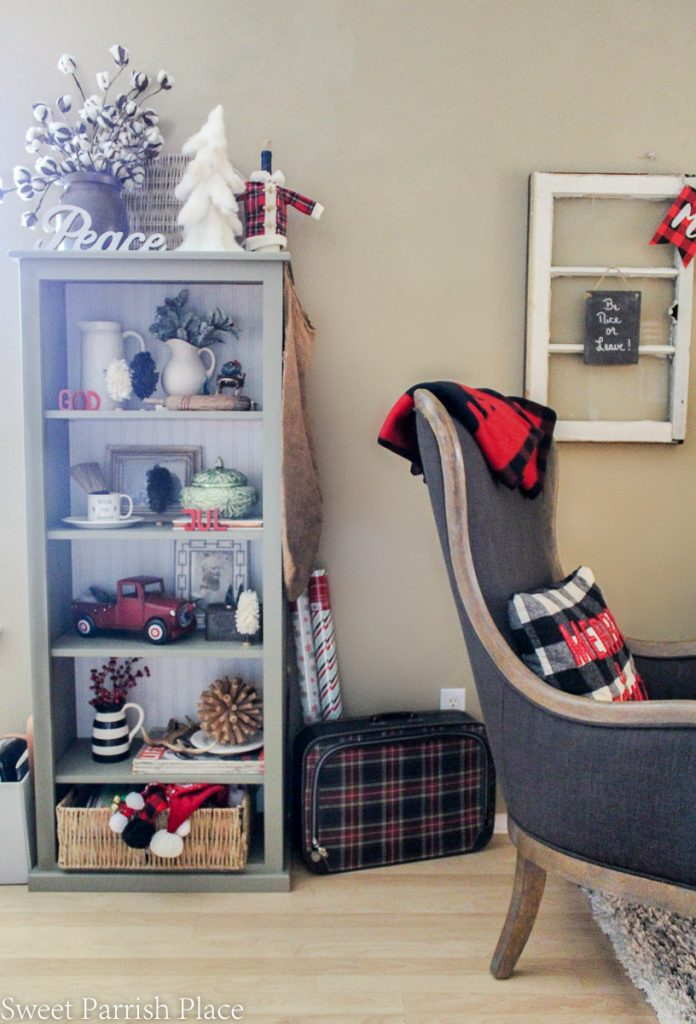 vintage plaid suitcase next to bookcase with Christmas decor