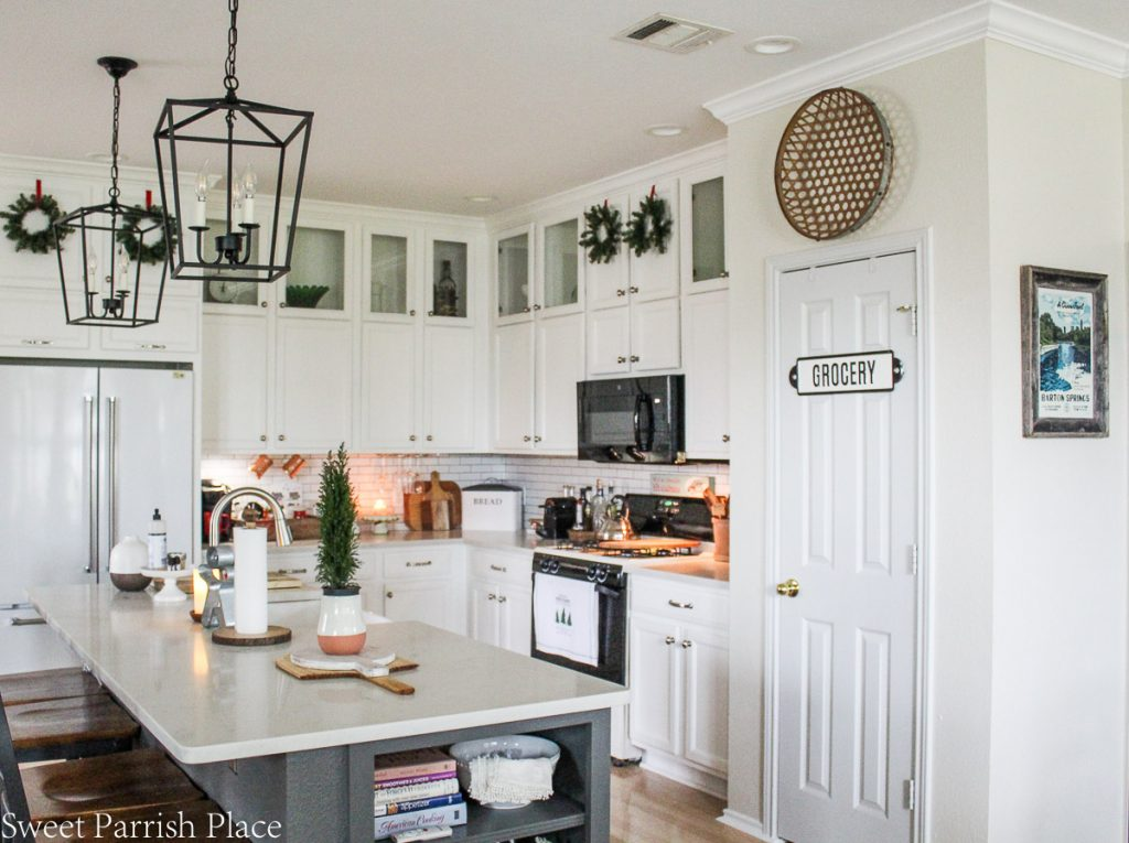 cozy and casual Christmas kitchen- white kitchen wth Christmas greenery